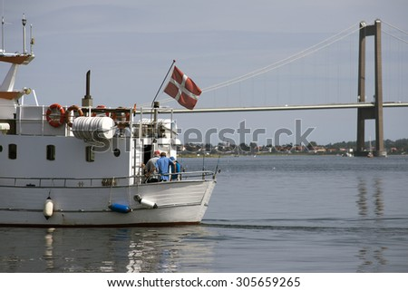 Fishing boat with fisher men. Boat with Danish flag close to Little Belt Bridge. - stock photo