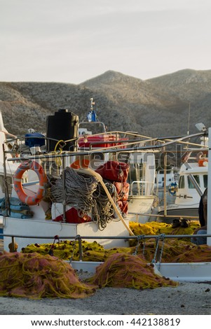 Fishing boat with yellow net with red floats in marine in greek island - stock photo