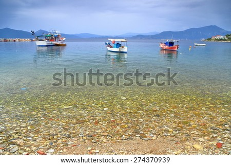 Fishing boats anchored floating on clear water of Aegean sea in overcast day, Agia Kiriaki, Greece - stock photo