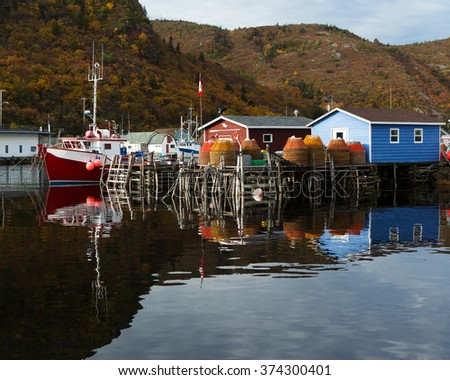 Fishing boats and stages with reflection. - stock photo