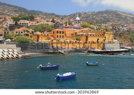 Fishing boats, city beach and ancient fortress. Funchal, Madeira, Portugal - stock photo