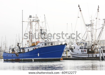 Fishing boats docked at a pier. - stock photo