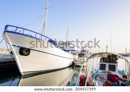 Fishing boats docked at the Limassol old port in Cyprus, next to the Marina part of the ports authority. A view of the harbor,the mediterranean sea, the water,boat and fish nets and fishing equipment. - stock photo