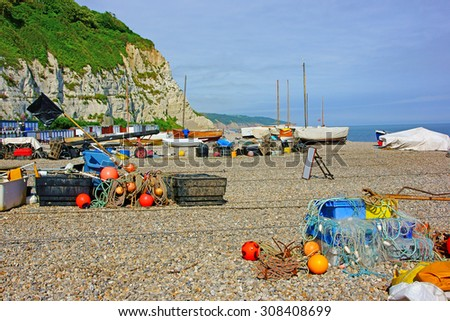 Fishing boats, fishing nets, lobster pots and floats on the beach near Budleigh Salterton, on a Summers day, Devon, United Kingdom. - stock photo