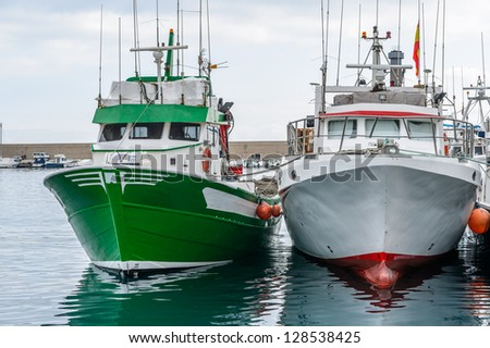 Fishing Boats in a Harbour and a Grey Sky - stock photo