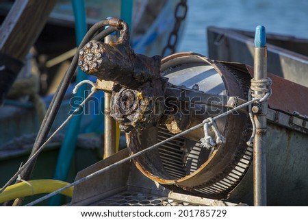 fishing boats in harbor - machine for the processing of clams - stock photo