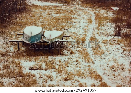 Fishing Boats in Tall yellow Grass with snow on the Shore - stock photo