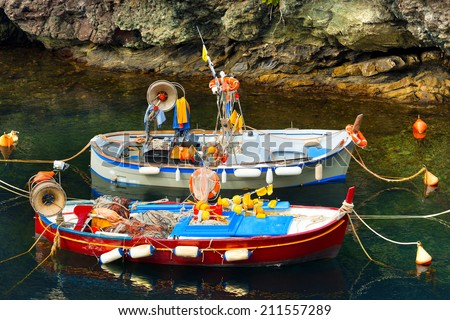 Fishing Boats in the Harbor - Liguria Italy / Two small fishing boats, red, blue and white with fishing equipment docked in port - Framura, La Spezia, Liguria, Italy - stock photo