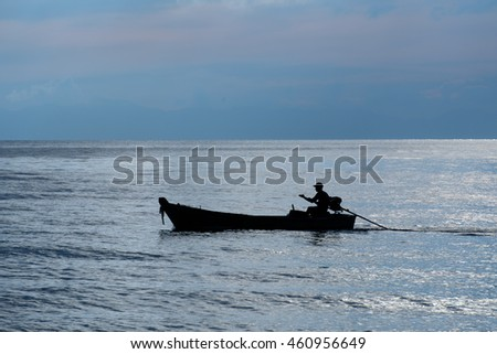 Fishing boats in the ocean at dusk .