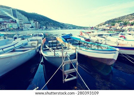Fishing boats lined up in wind sheltered bay - stock photo