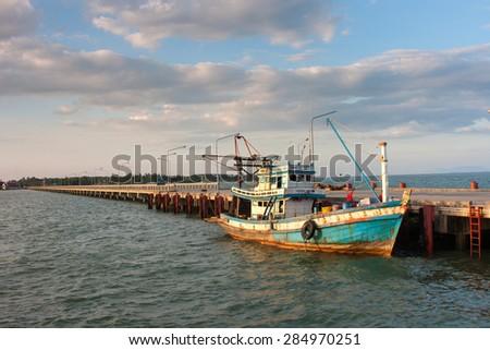 Fishing boats moored alongside the pier - stock photo