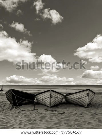 Fishing boats on a beach black and white, with cloudy sky  - stock photo