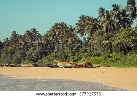 Fishing boats on a tropical beach with palm trees in the background - stock photo