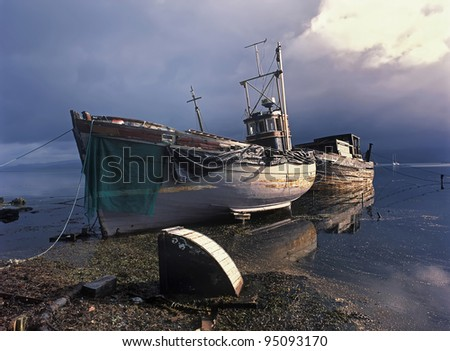Fishing boats on seashore after storm