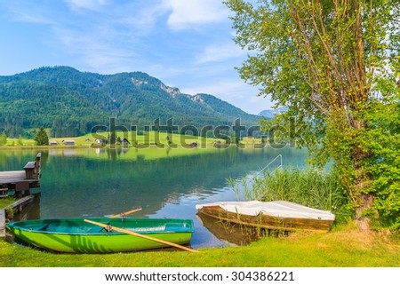 Fishing boats on shore of Weissensee lake in summer landscape of Carinthia land, Austria.
