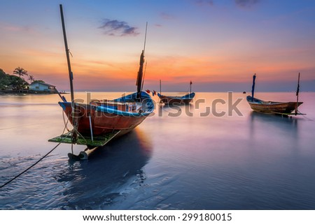 Fishing Boats on the Beach at sunset - stock photo