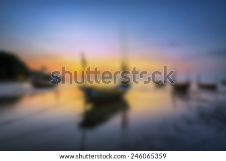Fishing Boats on the Beach at sunset blurry. - stock photo