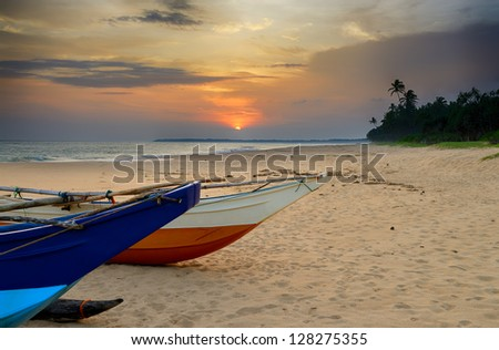 Fishing boats on the shore of the ocean. Tropical sunset - stock photo