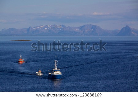 Fishing boats returning to port in Henningsvaer on Lofoten Islands, Norway - stock photo