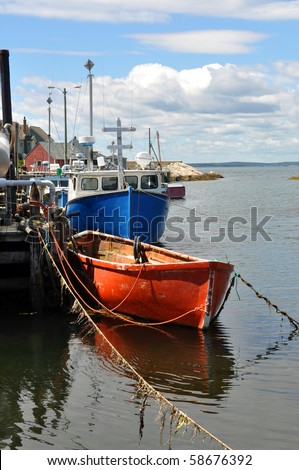 Fishing boats tied to wharf in scenic fishing village of Peggy's Cove, Nova Scotia - stock photo