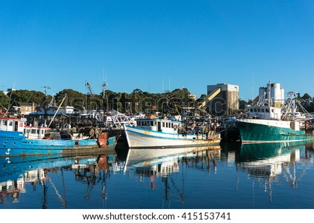 Fishing boats, trailers at port at day against clear blue sky on the background