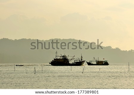 Fishing boats when sun rising up. Boats of group of fishermen going to sea - stock photo