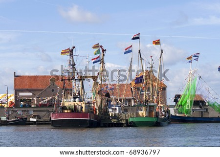 Fishing boats with flags in harbor of Enkhuizen in the Netherlands - stock photo