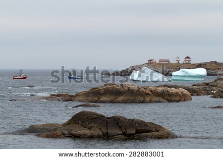 Fishing boats with iceberg and lighthouse in background. - stock photo