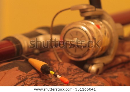 fishing bobber with a fishing rod(outfocus) on a camouflage background - stock photo
