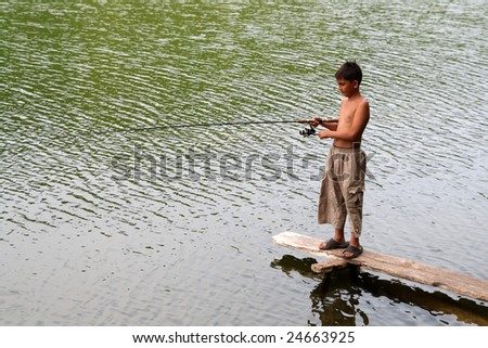 fishing boy on stage in lake - stock photo