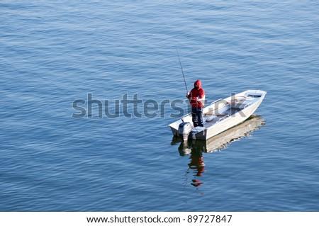 Fishing conceptual image - Fisherman in boat fishing - stock photo