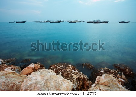 Fishing dhows at the harbour of the old pearling town of Al Wakrah in Qatar, Middle East, right before sunrise (movement on the Dhows) - stock photo