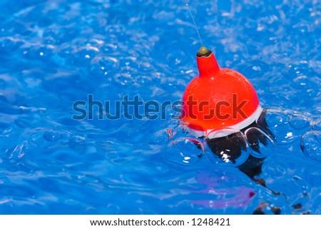 Fishing float in turbulent water - stock photo