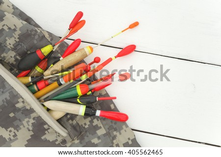 Fishing floats old and new, sticking out of the pocket light camouflage jacket, there is a place for inscriptions. White wooden background - stock photo