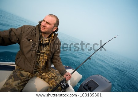 Fishing for salmon. Fisher holds a trolling rod. - stock photo