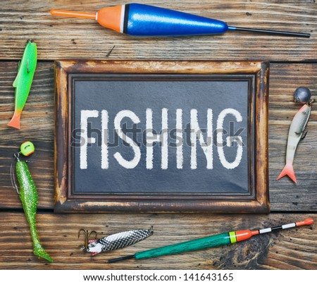 fishing gear and blackboard on wooden background - stock photo