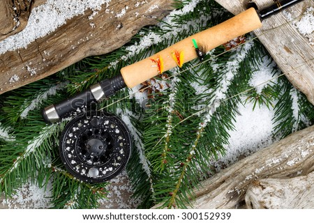 Fishing gear with evergreen branches and old driftwood covered in snow. - stock photo