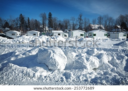 Fishing huts in the snow at Ste-Anne De La Perade in Quebec province, Canada. A village of small huts are assembled on the frozen river each year for the ice fishing season. - stock photo