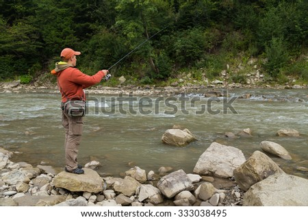 Fishing in the beautiful mountain river. Trout fishing in the mountains. Exciting fishing and beautiful scenery. Photos for natural and fishing magazines, posters and websites.