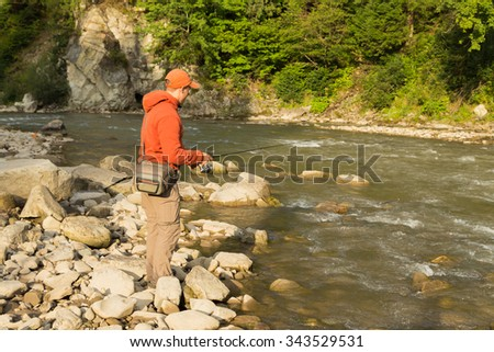 Fishing in the mountain river in summer. Fishing on the very beautiful mountain river. Trout fishing on spinning. Beautiful mountain scenery. Photo for fishing magazines, posters and websites. - stock photo