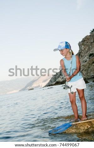 Fishing - little girl fishing at the beach - stock photo
