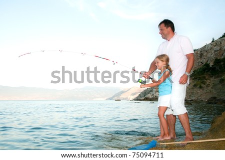 Fishing - little girl fishing with father at the beach - stock photo