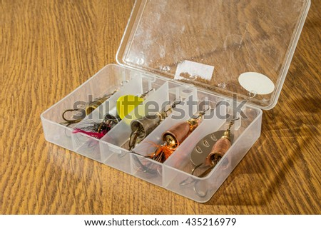 Fishing lures in the plastic box on old wooden table