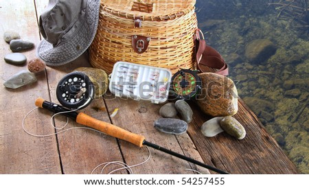 Fishing lures,reel,and sun hat near lake - stock photo