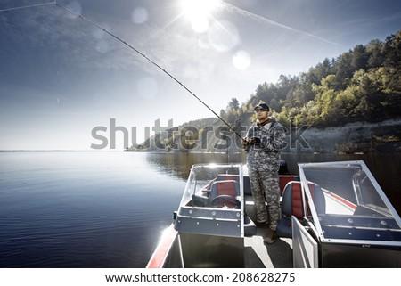 Fishing man in boat - stock photo