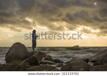 fishing man on rock sunset time
