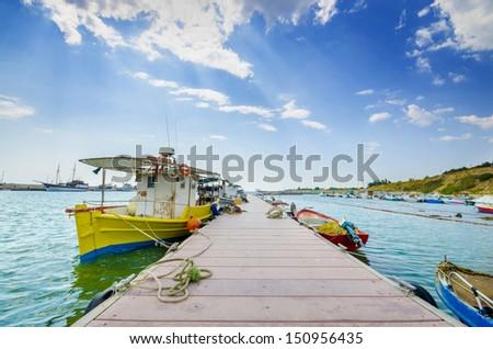 fishing marina boats on cloud blue sky and boardwalk - stock photo