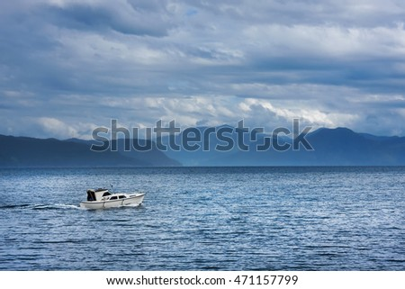 Fishing motor boat in waters of the Norwegian fjord in cloudy  weather