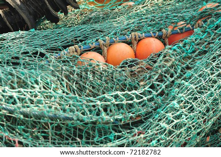 Fishing net and orange float on commercial fishing boat deck - stock photo