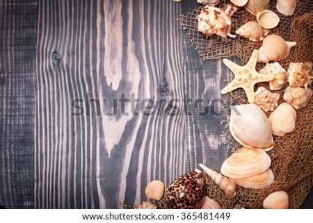 Fishing net and seashells on a wooden background - stock photo